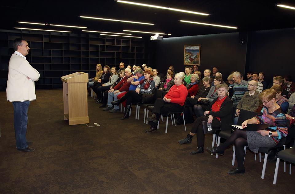 Esimene loeng. Esineja kõnepuldi kõrval. Rahvas istub toolidel.